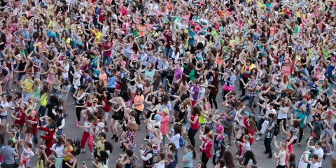 People perform a Gangnam style dance during a flash mob before the arrival of South Korean rapper Psy in Moscow